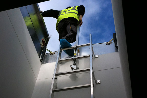 picture of man climbing a fixed vertical ladder through a roof access hatch